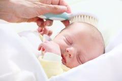 Baby hygiene. Mother brushing newborn's hair Stock Photo