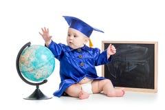 Baby im Akademiker kleidet mit Kugel an der Tafel stockfotos