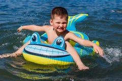 Baby im aufblasbaren Babyboot in Meer lizenzfreies stockbild
