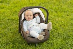 Baby im Autositz auf Gras Lizenzfreies Stockbild