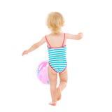 Baby im Badeanzug, der mit Kugel spielt. Hintere Ansicht Lizenzfreie Stockfotografie