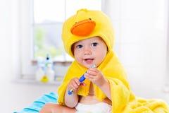 Baby im Badtuch mit Zahnbürste Stockfotografie