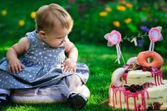 Baby im blauen Kleid sitzt auf grünem Gras nahe feierlichem Kuchen mit Nr. 1 Lizenzfreies Stockbild