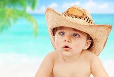Baby im Cowboyhut auf Strand Stockfoto