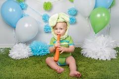 Baby im Feiertag Ostern-Häschenkostüm mit den großen Ohren, gekleidet im Grün kleidet das onesie und sitzt auf Wolldecke lizenzfreies stockbild