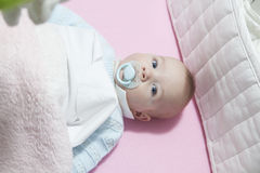 Baby im Feldbett mit Stoßauflage und Friedensstifter Lizenzfreie Stockfotografie