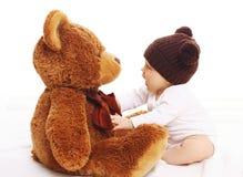 Baby im gestrickten braunen Hutspielen Lizenzfreie Stockfotos