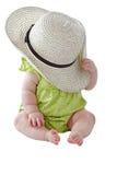 Baby im grünen Kleid spielt Peekaboo mit großem Strohhut Stockfotografie