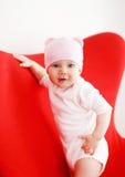 Baby im Hut, der auf dem Lehnsessel steht Lizenzfreie Stockfotografie