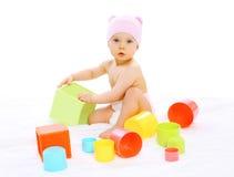 Baby im Hut, der mit buntem sitzt und spielt Stockfotografie