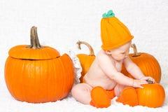 Baby im Kürbis-Hut, der nahe Kürbisen sitzt stockfotografie