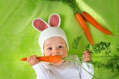 Baby im Kaninchenhut Karotte essend Stockbild