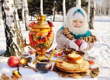 Baby im Mantel und Kopftuch im russischen Samowar im Ba lizenzfreie stockfotos