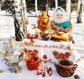 Baby im Mantel und Kopftuch im russischen Samowar im Ba stockfotos
