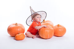 Baby im orange T-Shirt auf einem weißen Hintergrund, der in einem witche sitzt lizenzfreie stockbilder