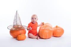 Baby im orange T-Shirt, das auf einem weißen Hintergrund umgeben sitzt Lizenzfreies Stockfoto