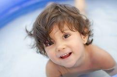 Baby im Plastikswimmingpool Stockfotos