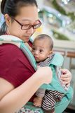 Baby im Riemen Innen Wenig Baby und ihre Mutter, die in Kaufhaus gehen lizenzfreies stockfoto