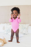 Baby im rosa babygro, das auf Bett steht stockfotos