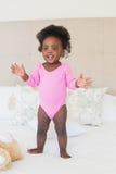 Baby im rosa babygro, das auf Bett steht stockbilder