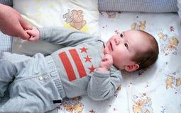 Baby im Säuglingsbett stockbild