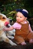 Baby im Schmutz mit Hund Stockbild