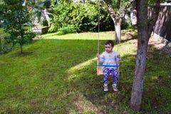 Kleines Mädchen im hölzernen Schwingen Lizenzfreies Stockbild