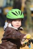 Baby im Sturzhelm erlernend, auf Fahrrad zu fahren Lizenzfreie Stockfotos