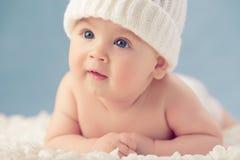 Baby im weißen Winterhut stockbilder