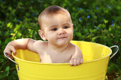 Baby with impish grin in yellow tub. A six month old baby boy sits in a big yellow bucket wearing an impish grin. He is not wearing a shirt. He is multicultural stock photos