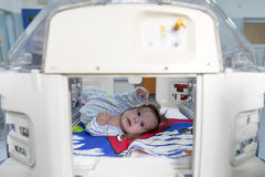 Baby in an incubator reaching out. Sofia, Bulgaria - March 1, 2016: A baby with a cardiac disease is reaching out of an incubator in a cardilogical children's Stock Photos