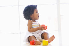Baby indoors playing with cup toys. Looking off camera Royalty Free Stock Photo