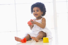 Baby indoors playing with cup toys royalty free stock images