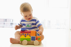 Baby indoors playing with truck Stock Photography