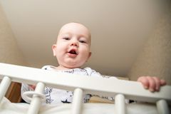 Baby infant boy in his bed. Standing portrait Royalty Free Stock Image
