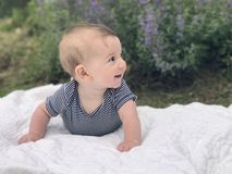 Infant baby boy laying on white quilt looking Royalty Free Stock Image