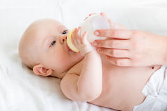 Baby infant eating milk. From bottle Royalty Free Stock Images
