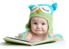 Baby infant in funny owl knitted hat owl with book on white background Stock Photo