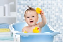 Baby kid taking bath, looking upwards and playing