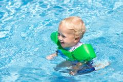 Baby with inflatable armbands in swimming pool. Little boy learning to swim in outdoor pool of tropical resort. Swimming with kids. Healthy sport activity for stock photography