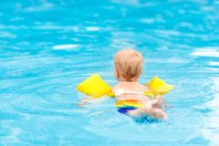 Baby in swimming pool. Kids swim. Baby with inflatable armbands in swimming pool. Little boy learning to swim in outdoor pool of tropical resort. Swimming with royalty free stock photos