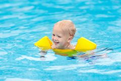 Baby in swimming pool. Kids swim royalty free stock images