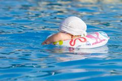Baby in inflatable tube is swimming in pool Royalty Free Stock Photo