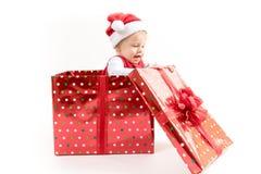 Baby innerhalb der Weihnachtsgeschenkbox öffnet Geschenk lizenzfreie stockfotografie