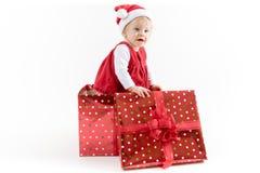 Baby innerhalb der Weihnachtsgeschenkbox, die beiseite schaut lizenzfreies stockbild