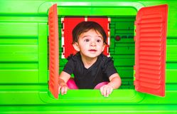 Baby inside toy house playhouse child look out the window stock photography