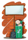 Baby inside the trashcan below  signboard Stock Images