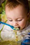 Baby isst Brei mit Brot von einer Glasplatte Stockbild