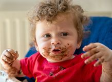 Baby isst einen Schokoladenkuchen Lizenzfreie Stockbilder