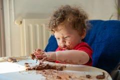 Baby isst einen Schokoladenkuchen Stockfotos